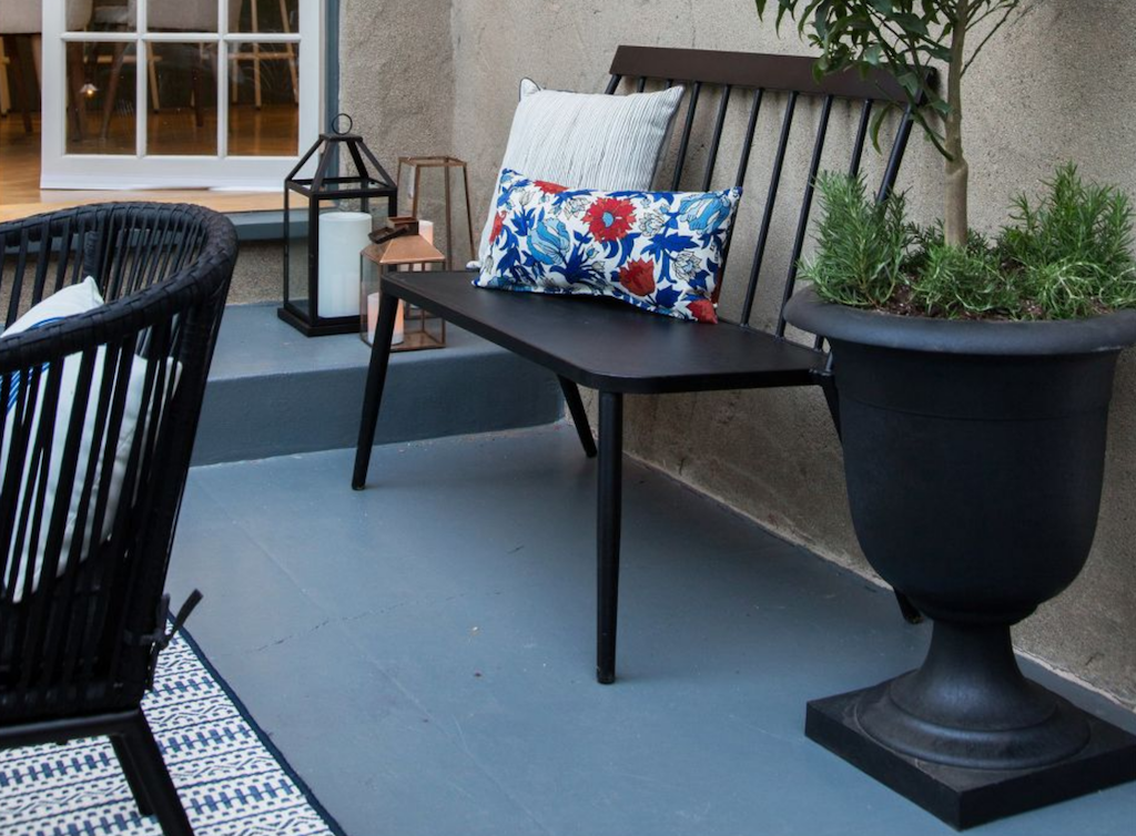 black patio bench on gray painted floor with colorful accent pillows