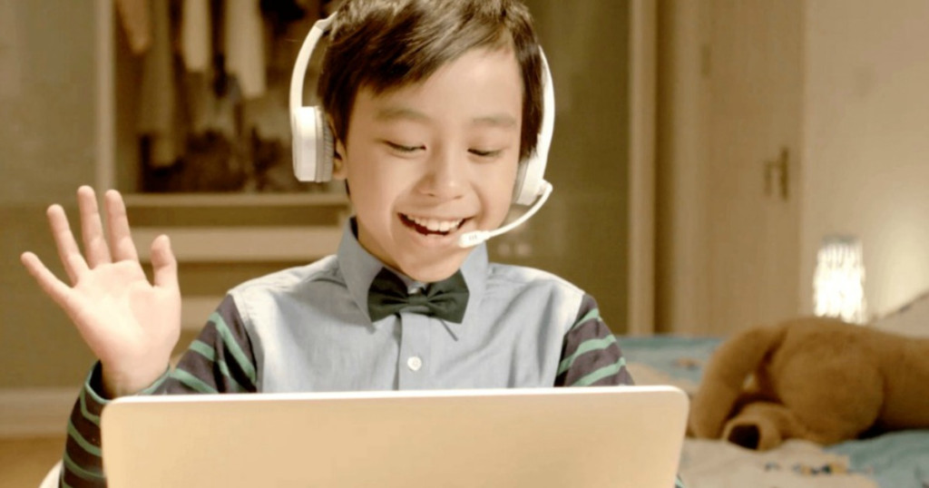 kid wearing headphones and looking at a computer