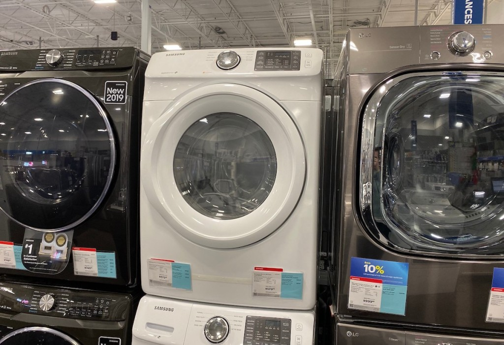 dark gray white and silver front load washing machine stacked next to each other in store aisle