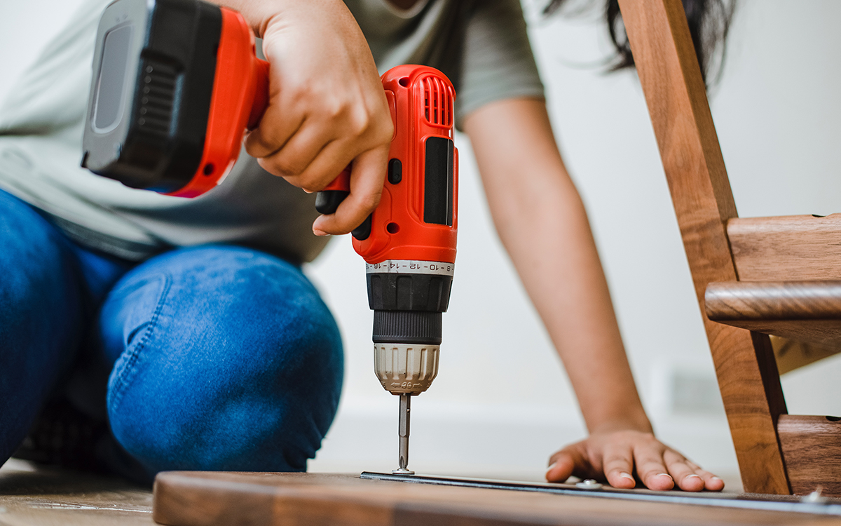 woman using a drill to assemble furniture
