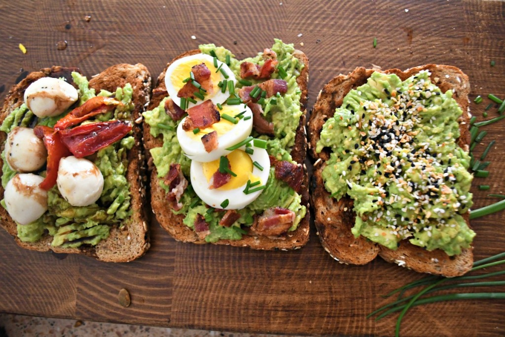 wood board with 3 examples of smashed avocado toast