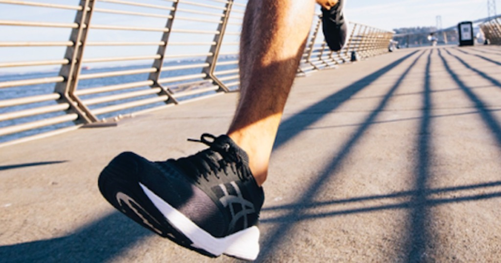 man running outside in black asics with white sole