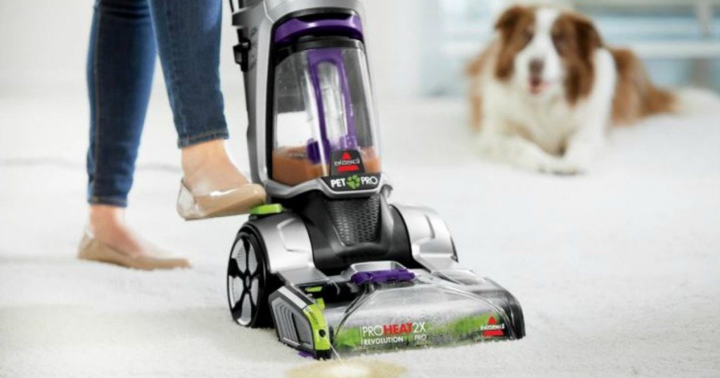 woman using a BISSELL ProHeat 2X Revolution Pet Pro Carpet Cleaner with dog in background