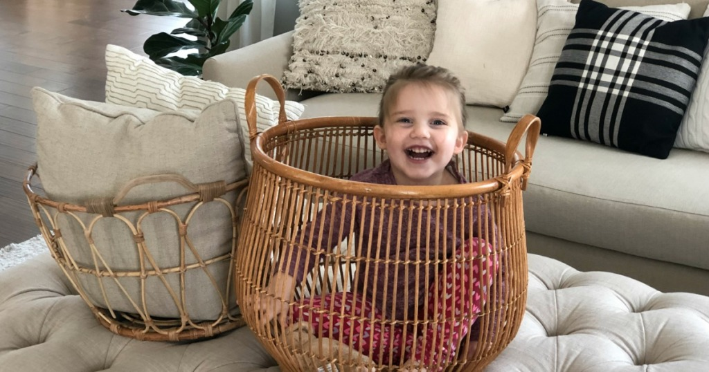 Child playing inside basket in living room