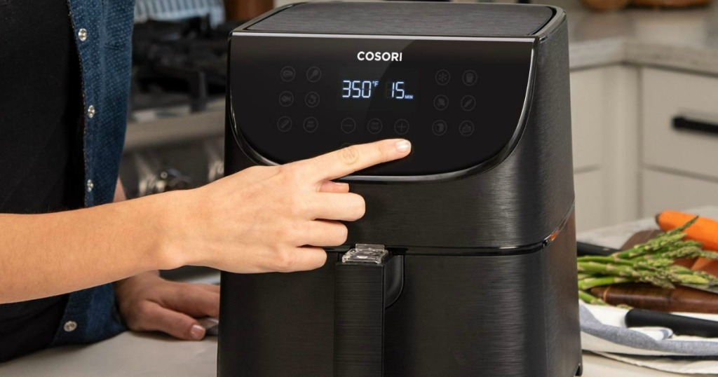 person pressing button on air fryer
