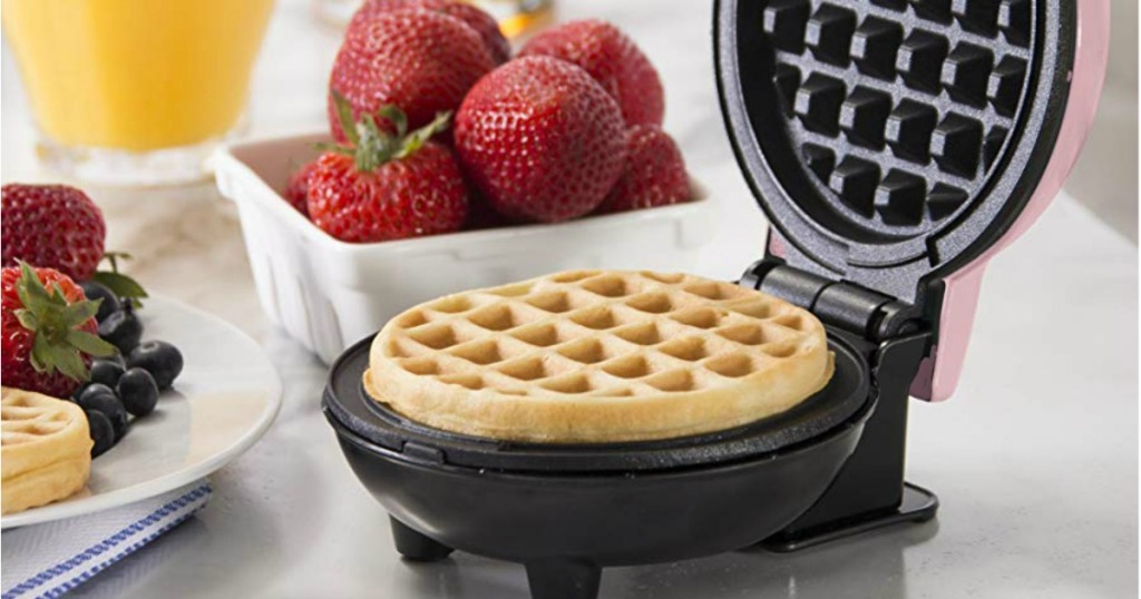 mini waffle maker with strawberries next to it