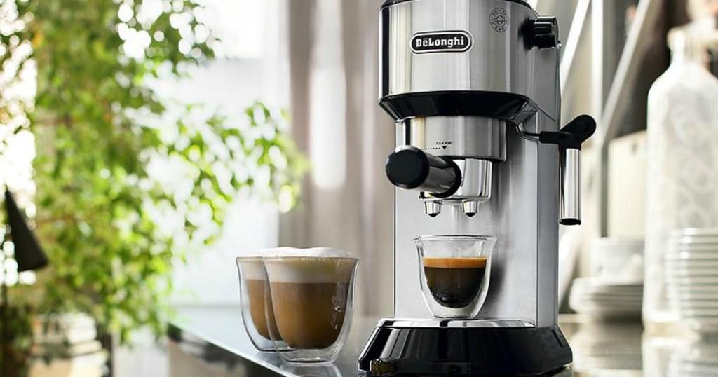 DēLonghi Dedica Espresso and Cappuccino Machine on counter with three glasses