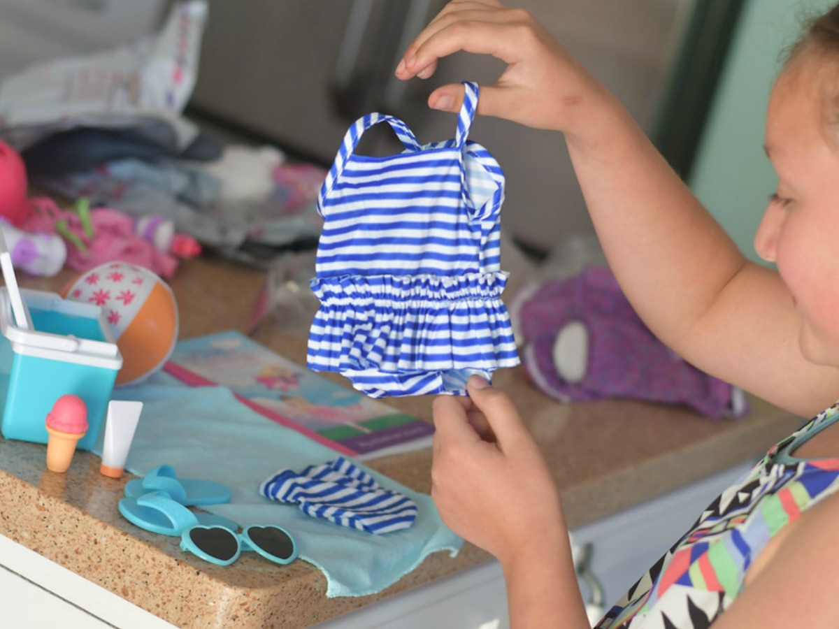 girl holding up a doll swimsuit