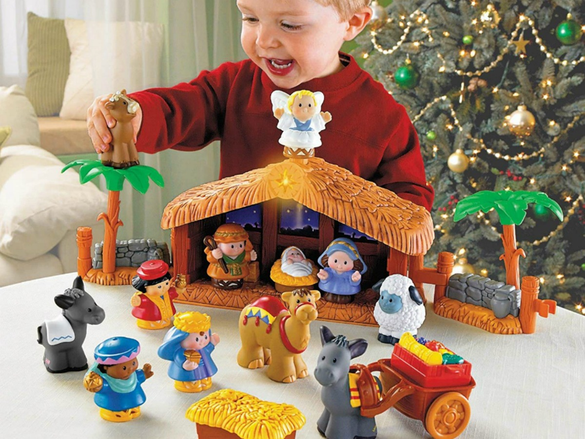 little boy playing with toy nativity set