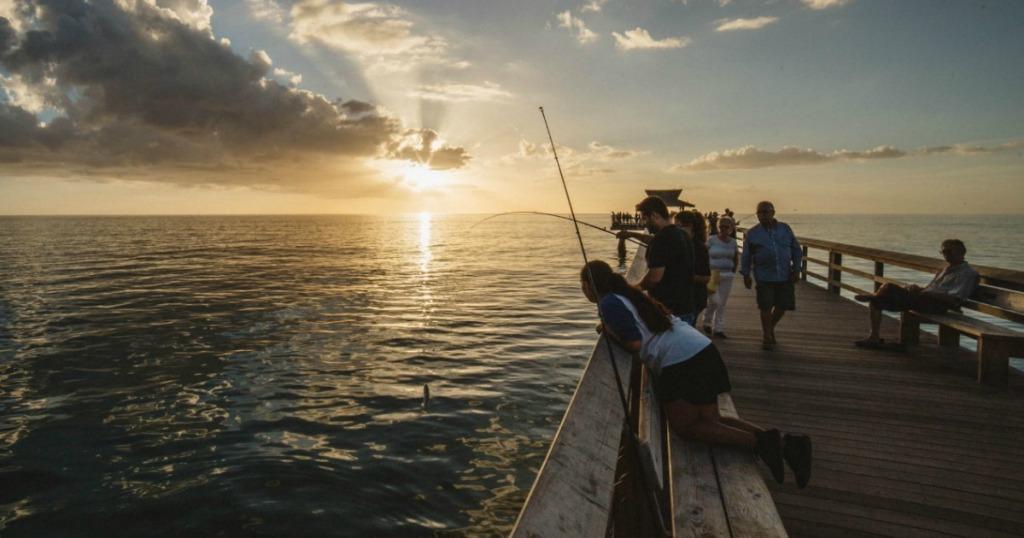 people on a fishing pier at sunset