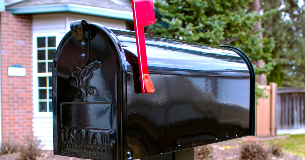 black mailbox outside with raised red flag on side