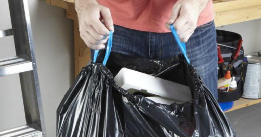 person pulling black hefty trash back up