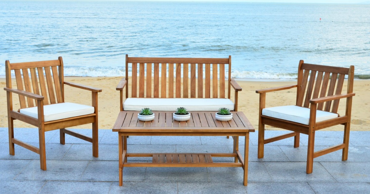 wooden outdoor patio set with chairs, table and sofa on a beach