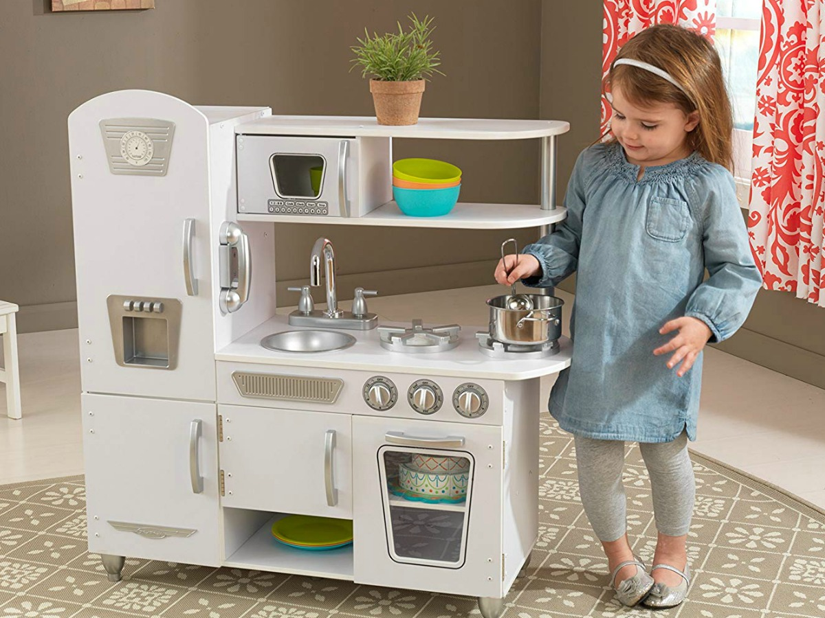little girl playing with KidKraft White Vintage Kitchen