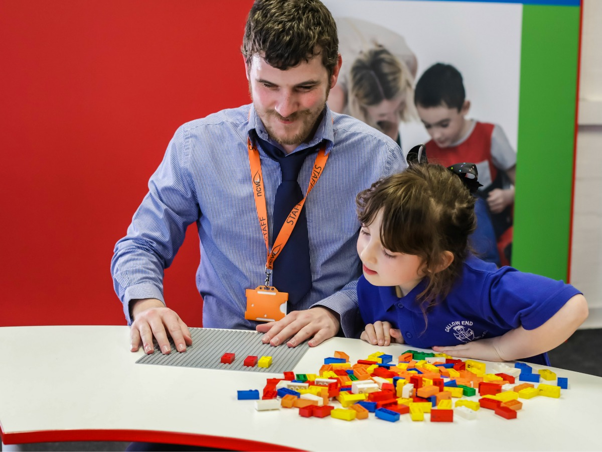 teacher and student playing with Legos