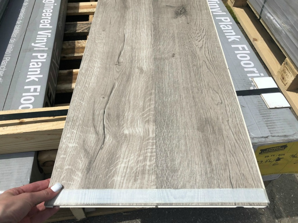 Lumber Liquidators Vinyl Plank Flooring Plank Held in Woman's Hand