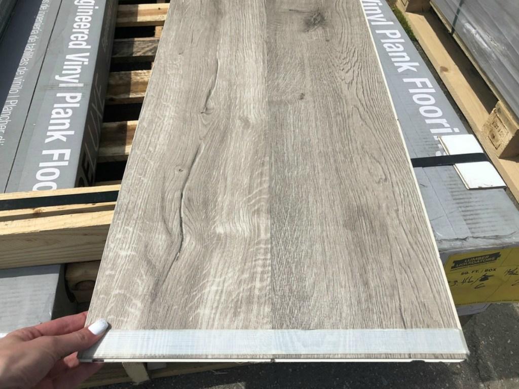 Lumber Liquidators Vinyl Plank Flooring Plank Held in Woman's Hand