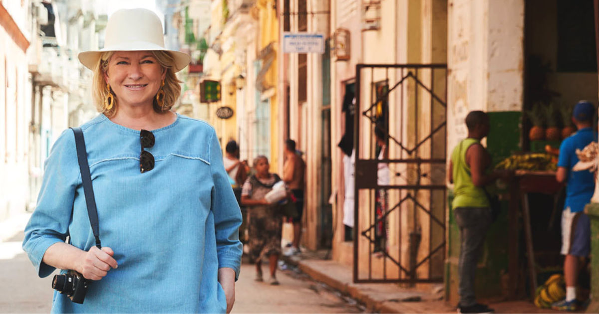 Martha Stewart in a hat standing with her camera