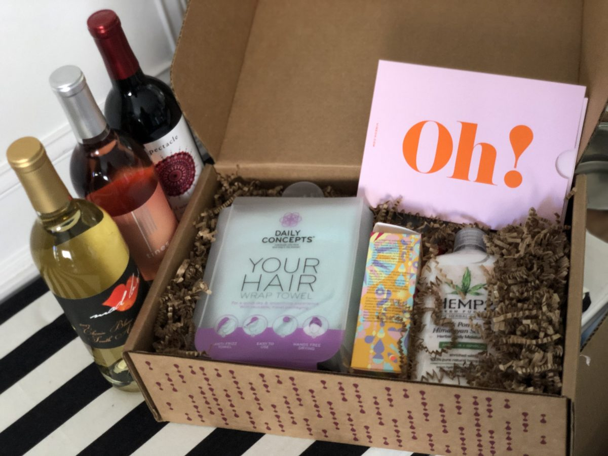 closeup of open box with wines, a card, and items inside