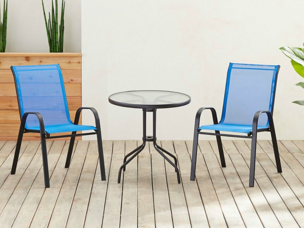 Two Pier1 Imports Sling Dining Chairs in blue on deck w/ a round table