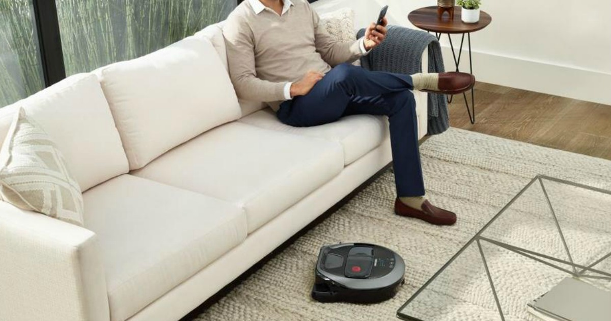 man sitting on a couch while a robotic vacuum cleans near his feet