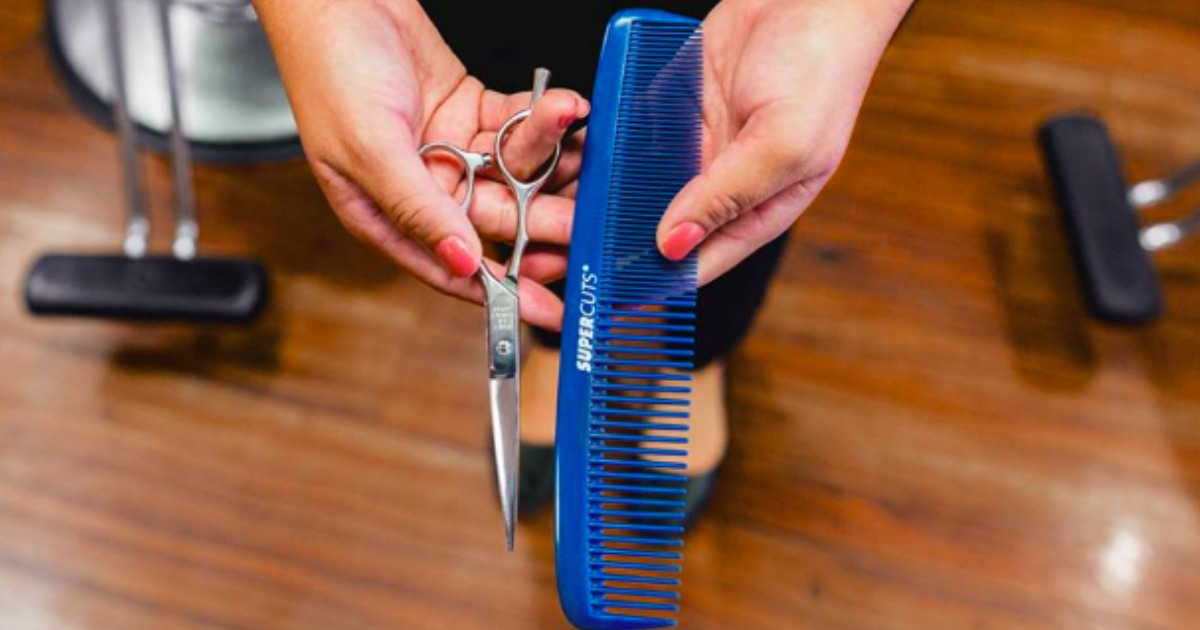 hand holding scissors and blue comb