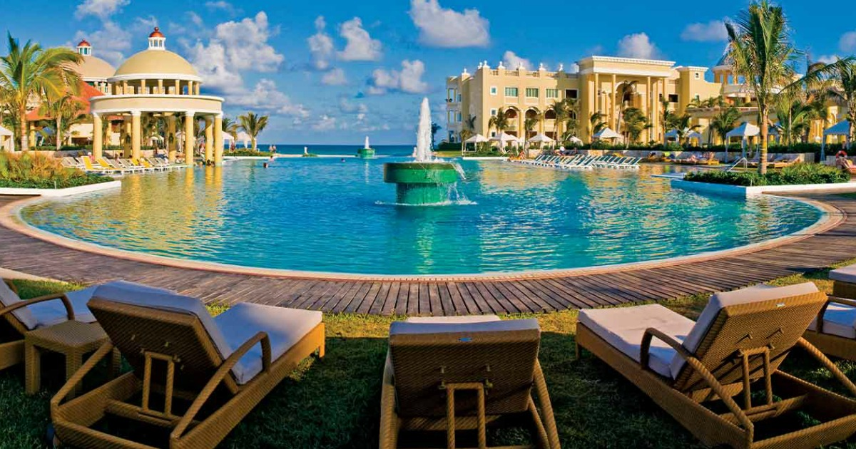 lounge chairs around a beautiful pool and fountain