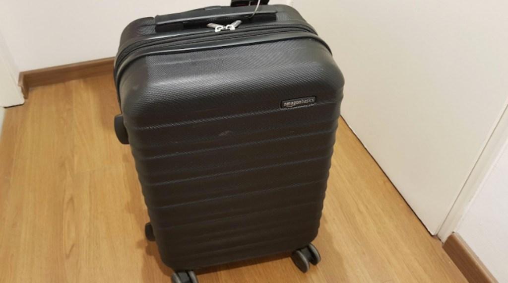 black luggage sitting on wood floor