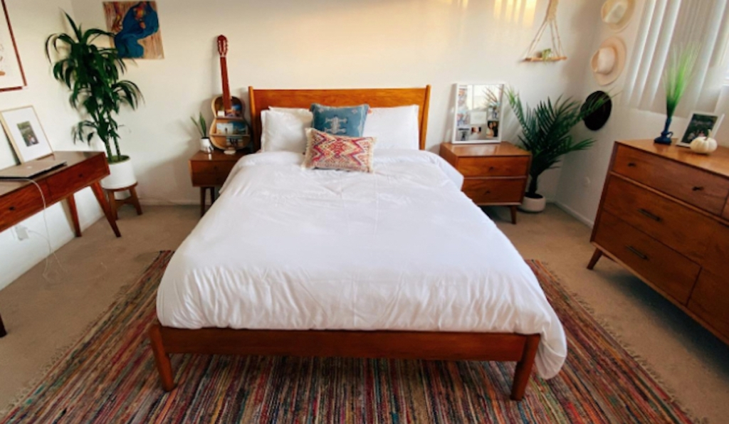 bedroom with white duvet cover on bed and various boho decor