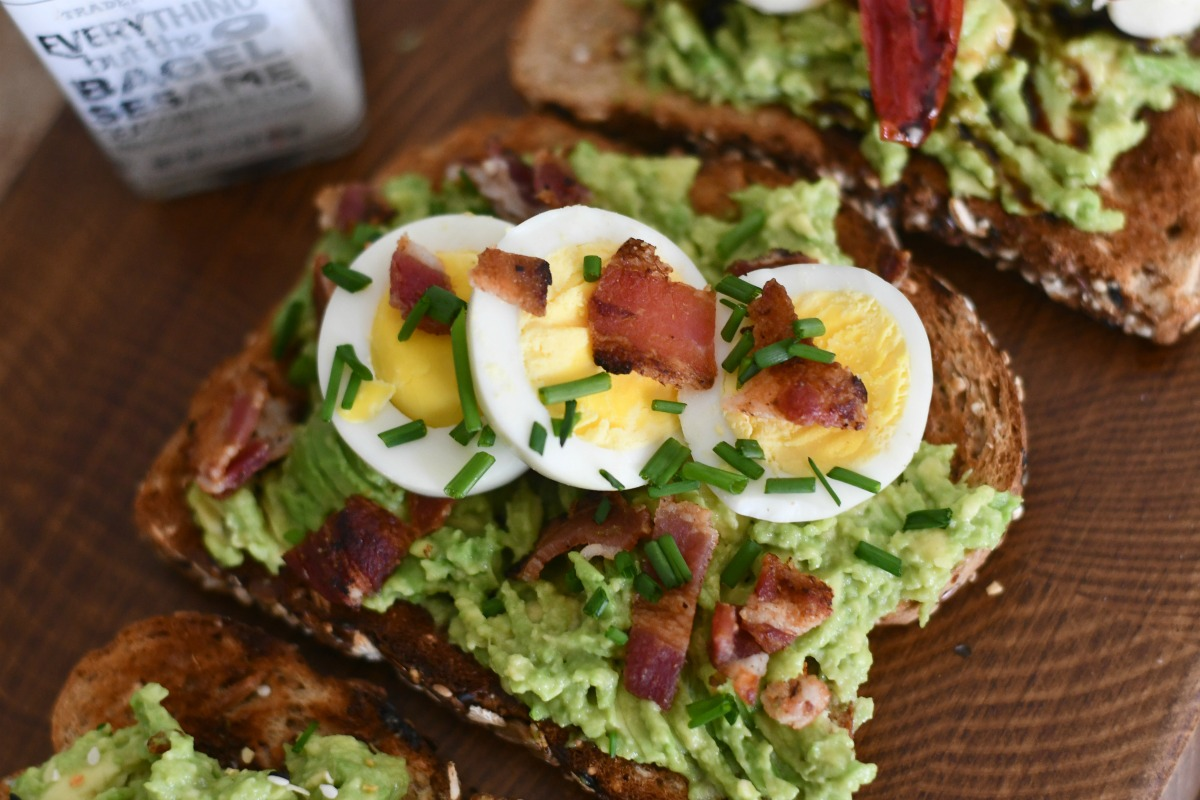 bacon and egg avocado toast with fresh chive garnish