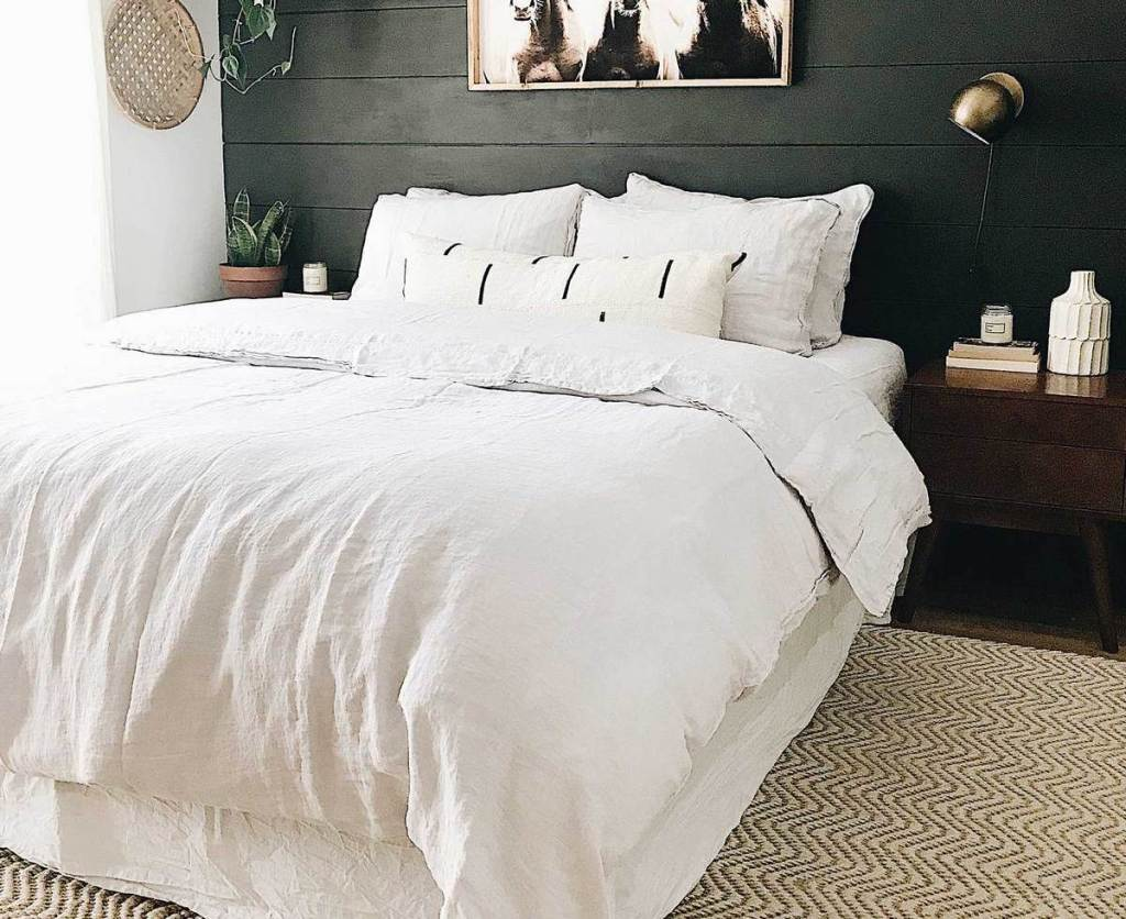bedroom with white bed and pillows with dark accent wall behind it