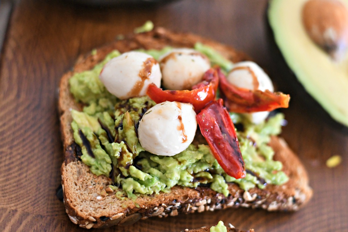 mozzarella cheese and roasted tomato avocado toast on a wood board