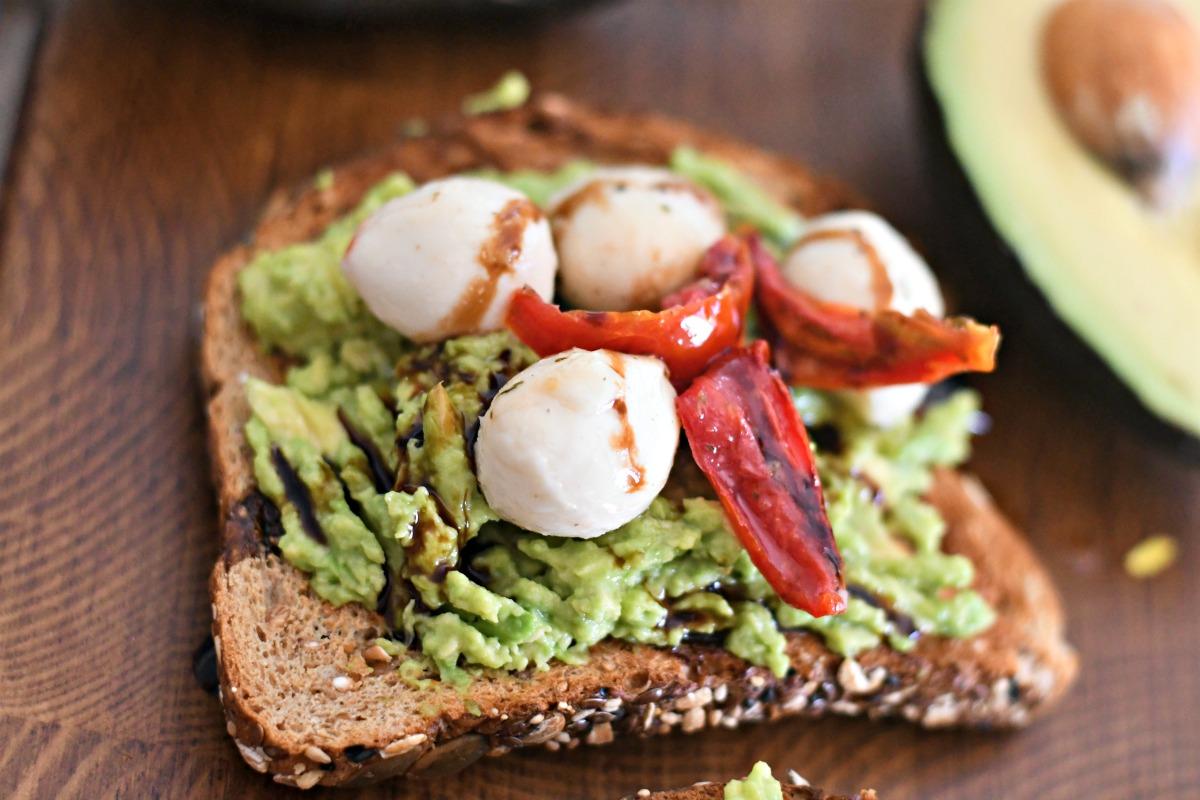 mozzarella cheese and roasted tomato avocado toast on a wood board