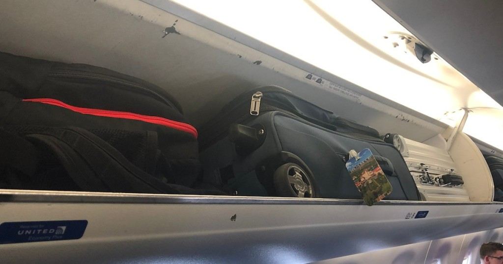 three suitcases luggage in overhead compartment on airplane