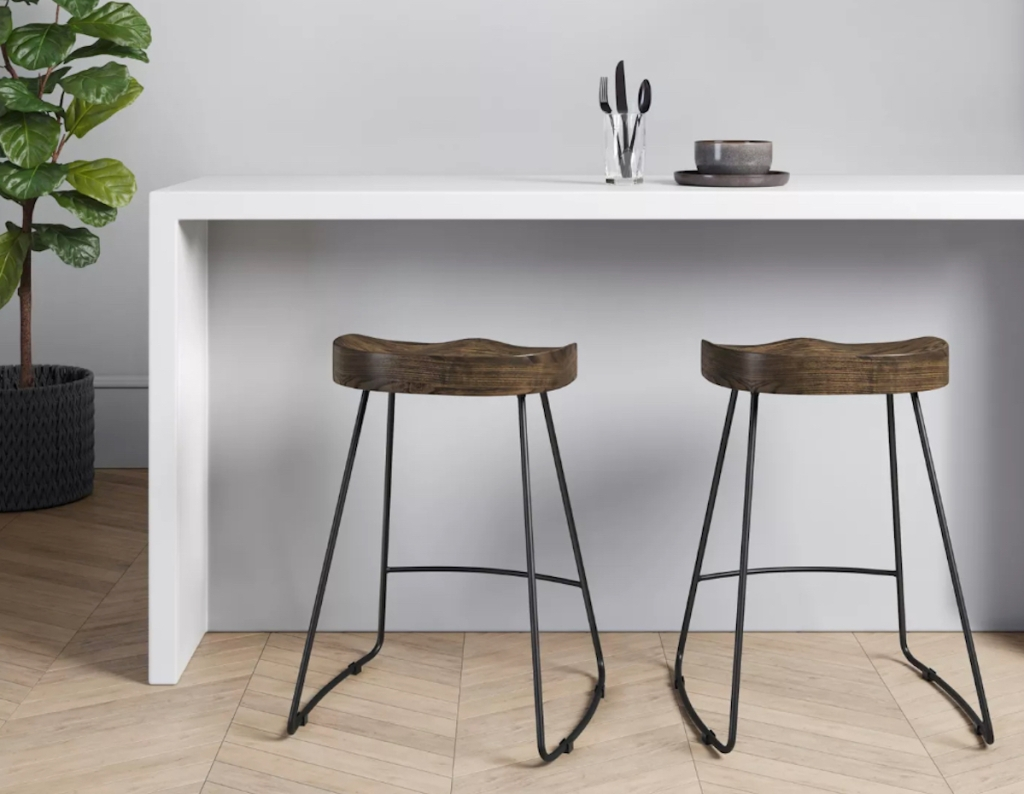 two wood counter stools sitting at white kitchen island counter