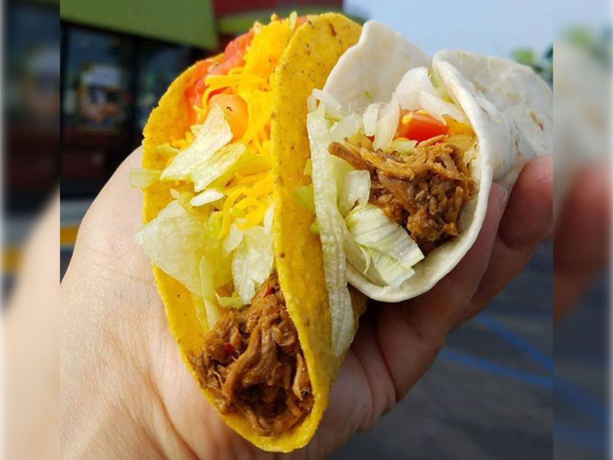 hand holding 2 del taco tacos