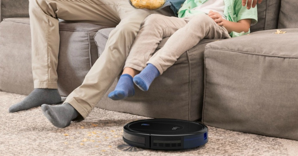 people sitting on the couch lifting their feet for the eufy robotic vacuum