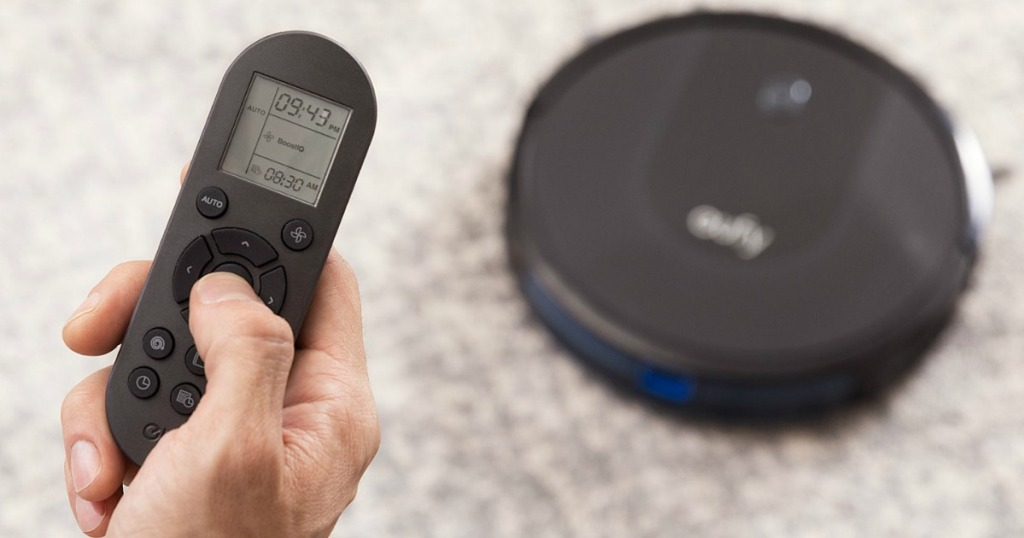 hand holding remote to eufy robotic vacuum with vacuum on the floor