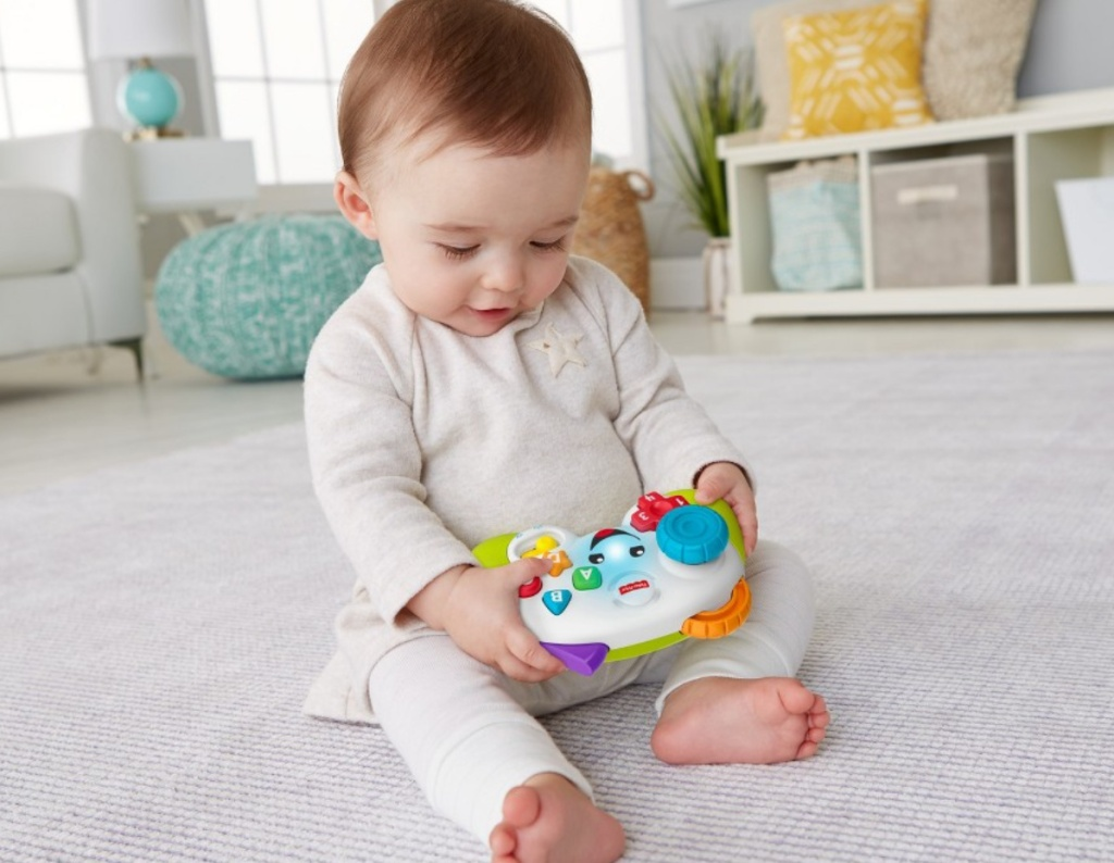 baby playing with fisher price laugh and learn controller