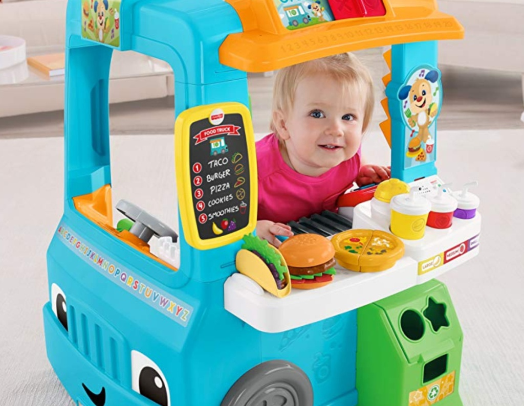 Fisher-Price Laugh and Learn Servin' Up Fun Food Truck with a toddler inside playing