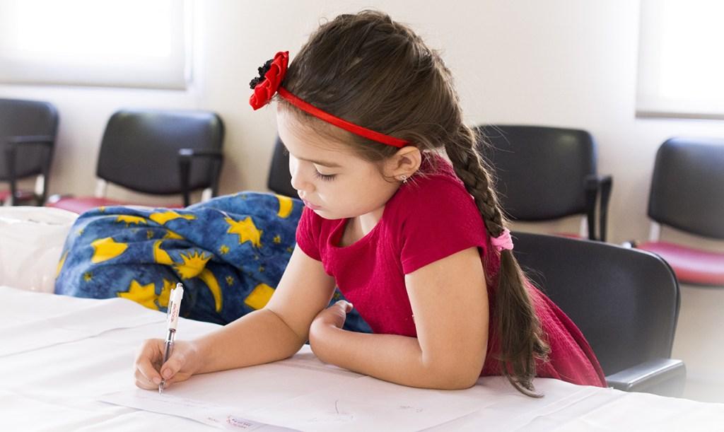 little girl writing on paper