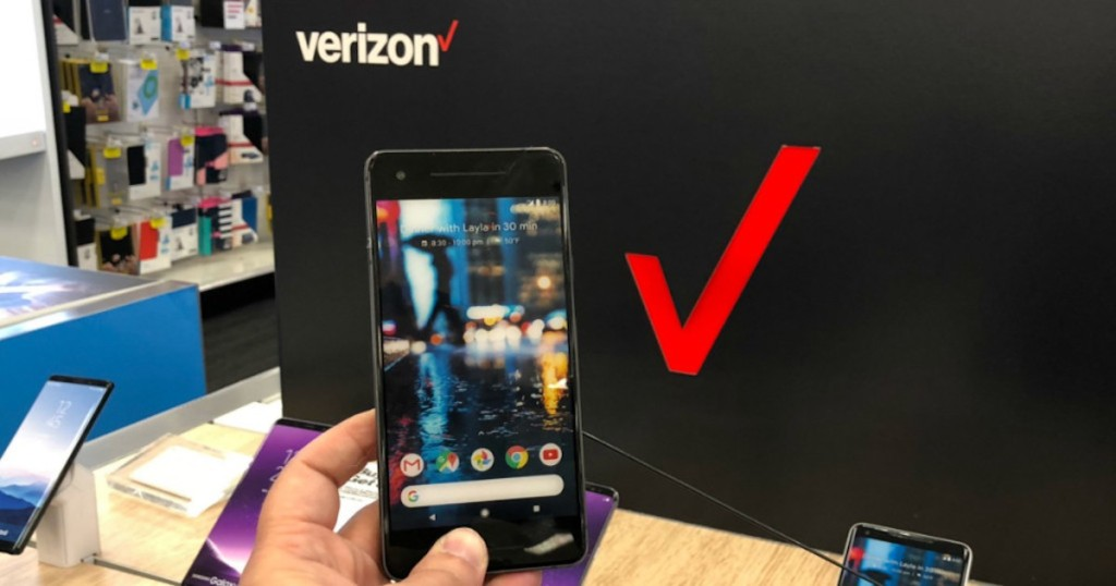 hand holding google pixel phone in front of verzion sign