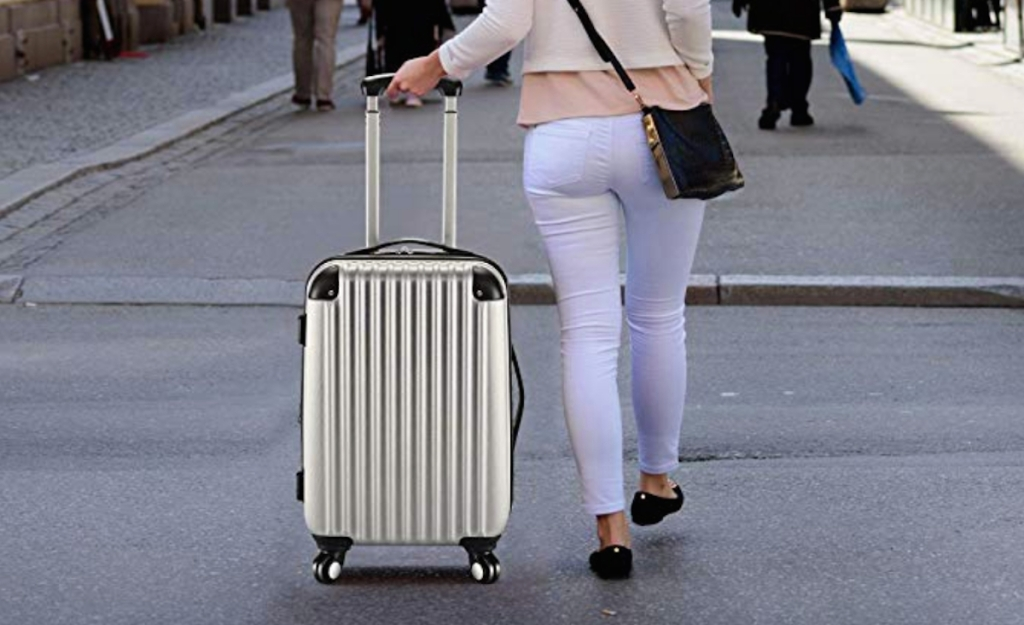 woman walking through city pulling silver luggage behind her