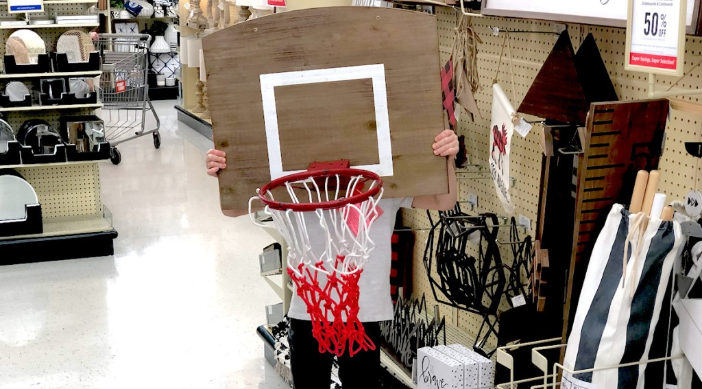 kid holding up a wooden basketball hoop in store aisle - kids decor themes hobby lobby