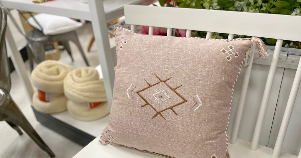 pink pillow sitting on white bench with rolled cream throw blankets in the background