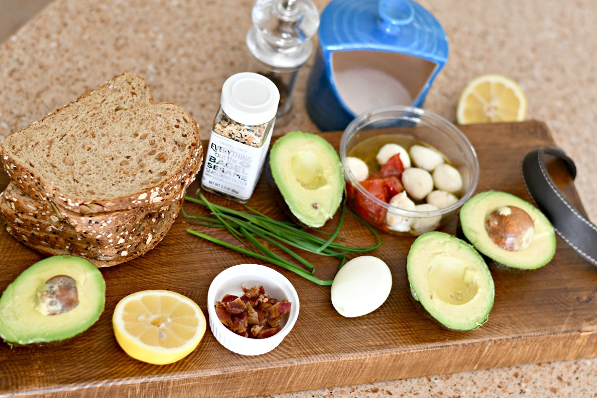 ingredients to make avocado toast recipes on a wood serving board