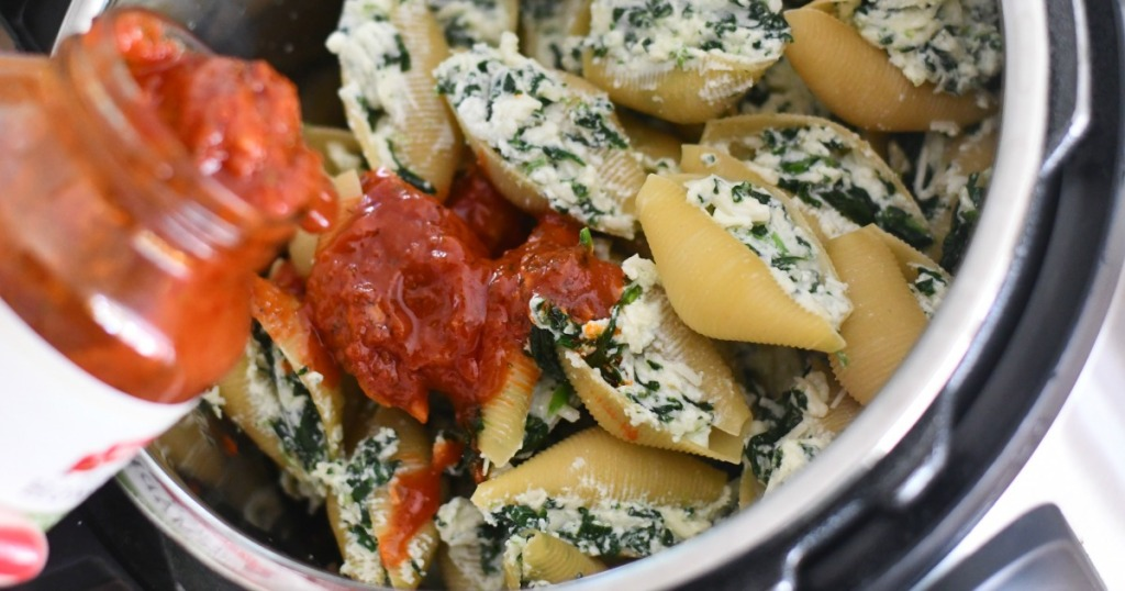pouring marinara sauce over stuffed shells using the instant pot