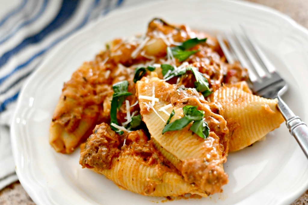 spinach and cheese stuffed shells on a white plate