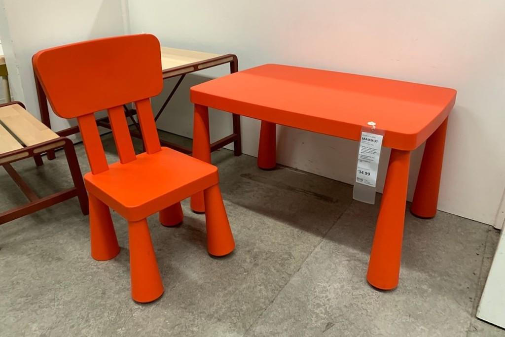 red kids size table and chair sitting on concrete floor in store