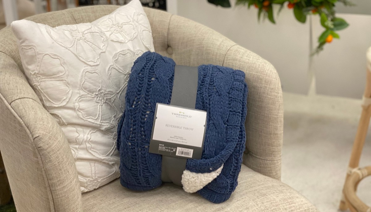 blue cable knit blanket rolled up on tufted cream accent chair with white pillow